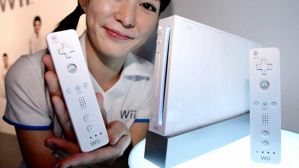 """A model displays Japanese video game giant Nintendo's new video game console """"Wii"""" and its controler during a press preview at Makuhari, suburban Tokyo, 14 September 2006. Nintendo will put it on the market 02 December with a price of 25,000 yen (220 USD).    AFP PHOTO / YOSHIKAZU TSUNO / AFP PHOTO"""