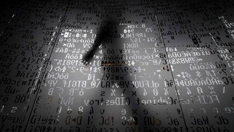 A picture taken on October 17, 2016 shows an employee walking behind a glass wall with machine coding symbols at the headquarters of Internet security giant Kaspersky in Moscow. / AFP PHOTO / Kirill KUDRYAVTSEV / TO GO WITH AFP STORY BY Thibault MARCHAND