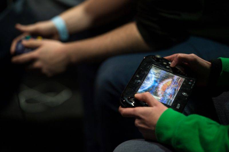 A competitor plays on a Wii U console as he takes part in the 'King of the North' gaming festival held at the Manchester Academy venue in Manchester, northern England on March 22, 2017. King of the North hosts the grand finals of the UK's largest student e-sports tournament as well as computer game and board game competitions. / AFP PHOTO / Oli SCARFF