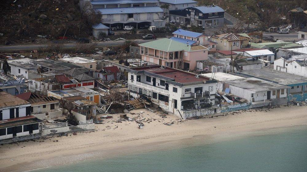 This aerial view shows buildings destroyed by Hurricane Irma on the French Caribbean island of Saint Martin on September 12, 2017, during the visit of France's President Emmanuel Macron.  French President Emmanuel Macron and British Foreign Secretary Boris Johnson travelled Tuesday to the hurricane-hit Caribbean, rebuffing criticism over the relief efforts as European countries boost aid to their devastated island territories. / AFP PHOTO / POOL / Christophe Ena