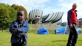 """A migrant man and child pose next to tent shelters installed by a group of migrants on the campus of the University of Reims in Reims, northeastern France, on September 18, 2017.  Courses at the University of Reims are suspended """"until further notice"""" due to the presence of migrants on the campus, a measure that affects about 8,000 student on September 18. """"Access to the university premises located on the Red Cross campus is forbidden until security conditions are restored,"""" the president of the university, Guillaume Gelle, in a decree signed September 17 and transmitted to the AFP. / AFP PHOTO / FRANCOIS NASCIMBENI"""