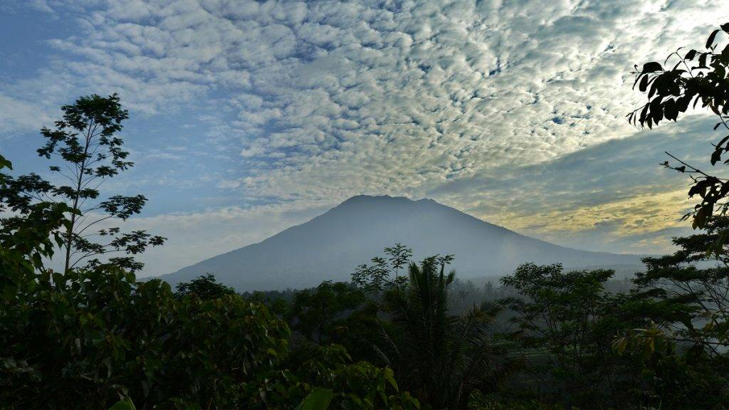 A general view shows Mount Agung from Karangasem on the Indonesian resort island of Bali on September 24, 2017.  Authorities have raised alert levels for a volcano on the Indonesian resort island of Bali after hundreds of small tremors stoked fears it could erupt for the first time in more than 50 years. / AFP PHOTO / SONNY TUMBELAKA