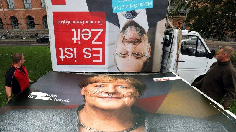 Workers carry away a CDUcampaign poster that shows Chancellor Merkel and pass by a SPDposter with Schulz's face on it in Berlin, Germany, 25 September 2017. Photo: Wolfgang Kumm/dpa