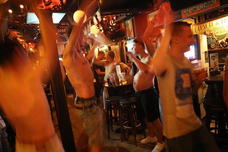 """PALMA DE MALLORCA, SPAIN - JULY 25:  Dutch-speaking visitors party in a pub on the Ballermann stretch on July 25, 2017 in Palma de Mallorca, Spain. The term Ballermann, which combines the Spanish word for bathing site """"balneario"""" and the German slang word for heavy drinking """"ballern,"""" has become synonymous with the party atmosphere of the beach-front street. The stretch is especially popular among young German and Dutch tourists, who spend the days at the beach and the nights in the pubs and discos.  (Photo by Sean Gallup/Getty Images)"""