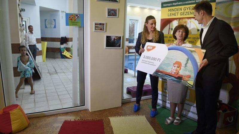 Budakalász, 2017. szeptember 13. Hosszú Katinka háromszoros olimpiai bajnok  úszó (b) és Szollár Domokos, a MOL-csoport kommunikációs igazgatója átadja a hárommillió forintos adományt Schultheisz Judit orvosigazgatónak, a Gézengúz Alapítvány alapítójának az alapítvány kisgyermekeken segítõ hidroterápiás részlegében Budakalászon, a Cseppek Házában 2017. szeptember 13-án. MTI Fotó: Koszticsák Szilárd
