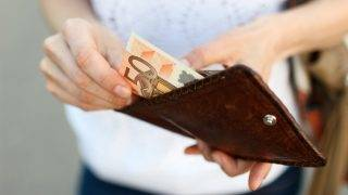 Girl is taking out a banknote of fifty euros from brown leather wallet on the street. Hands, money and wallet close-up