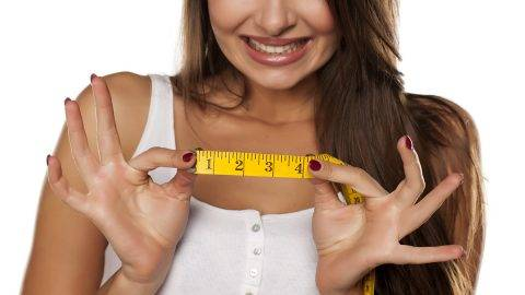 young woman makes fun of the length of measuring tape