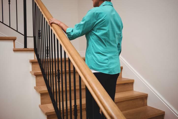 Senior woman walking up stairs at home