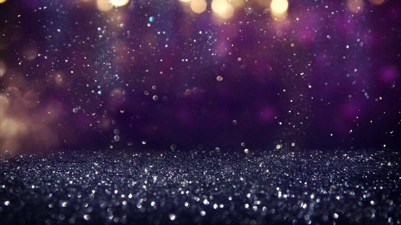 glitter vintage lights background. gold, purple and black. de-focused.