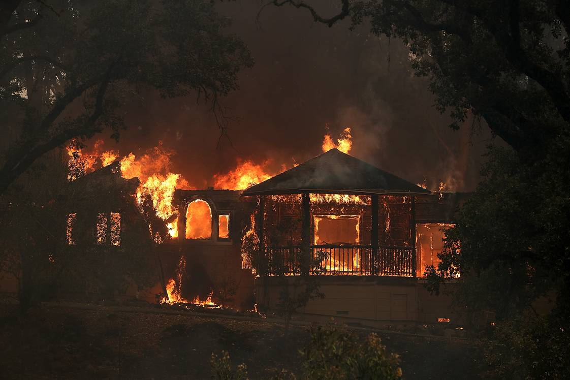 GLEN ELLEN, CA - OCTOBER 09:  Flames consume a home as an out of control wildfire move through the area on October 9, 2017 in Glen Ellen, California. Tens of thousands of acres and dozens of homes and businesses have burned in widespread wildfires that are burning in Napa and Sonoma counties.   (Photo by Justin Sullivan/Getty Images)