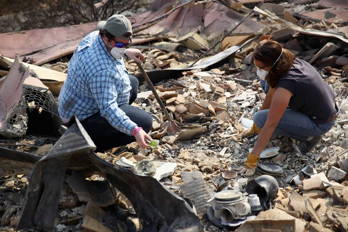 NAPA, CA - OCTOBER 10:  Brad Turley and Charisse Desmarais look through the remants of her mother's home in the Silverado Community, which was burned by the Atlas Fire on October 10, 2017 in Napa, California. Fifteen people have died in wildfires that have burned tens of thousands of acres and destroyed over 2,000 homes and businesses in several Northen California counties.  (Photo by Ezra Shaw/Getty Images)