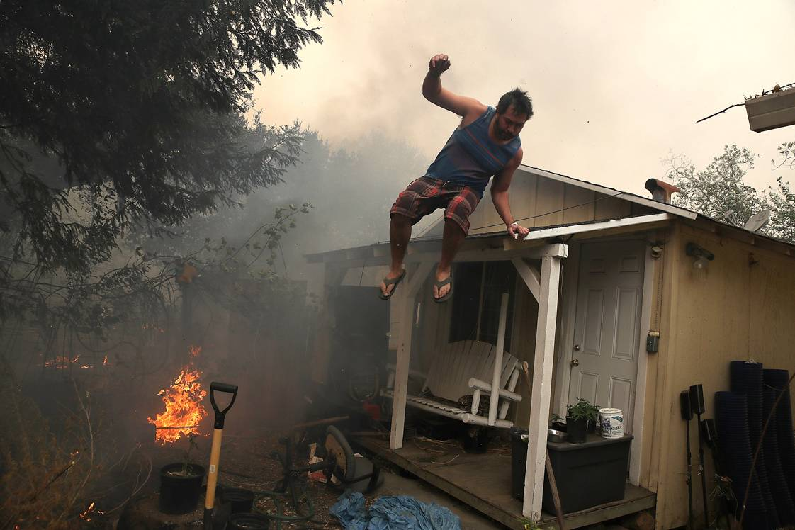 GLEN ELLEN, CA - OCTOBER 09:  A resident rushes to save his home as an out of control wildfire moves through the area on October 9, 2017 in Glen Ellen, California. Tens of thousands of acres and dozens of homes and businesses have burned in widespread wildfires that are burning in Napa and Sonoma counties.  (Photo by Justin Sullivan/Getty Images)