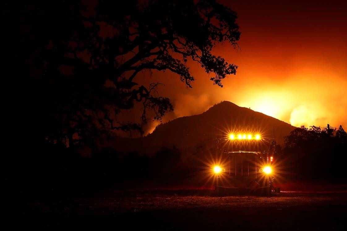KENWOOD, CA - OCTOBER 10:  A fuel truck sits in a stagin area as the Nuns Fire burns in the hills behind it on October 10, 2017 in Kenwood, California. Fifteen people have died in wildfires that have burned tens of thousands of acres and destroyed over 2,000 homes and businesses in several Northen California counties.  (Photo by Justin Sullivan/Getty Images)