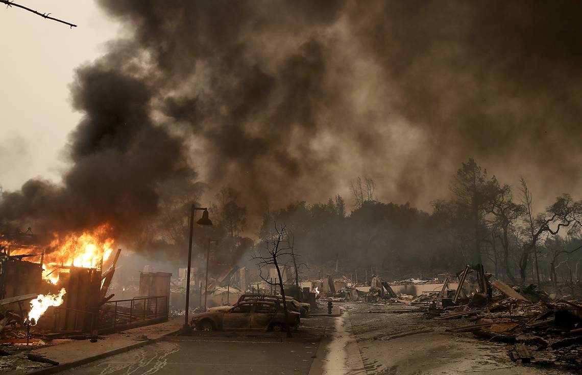 SANTA ROSA, CA - OCTOBER 09:  Burned out cars sit next to a building on fire in a fire ravaged neighborhood on October 9, 2017 in Santa Rosa, California. Ten people have died in wildfires that have burned tens of thousands of acres and destroyed over 1,500 homes and businesses in several Northen California counties.  (Photo by Justin Sullivan/Getty Images)