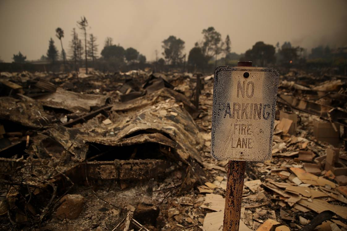 SANTA ROSA, CA - OCTOBER 09:  A sign stands next to fire damaged mobile homes at the Journey's End Mobile Home Park on October 9, 2017 in Santa Rosa, California. Ten people have died in wildfires that have burned tens of thousands of acres and destroyed over 1,500 homes and businesses in several Northen California counties.  (Photo by Justin Sullivan/Getty Images)