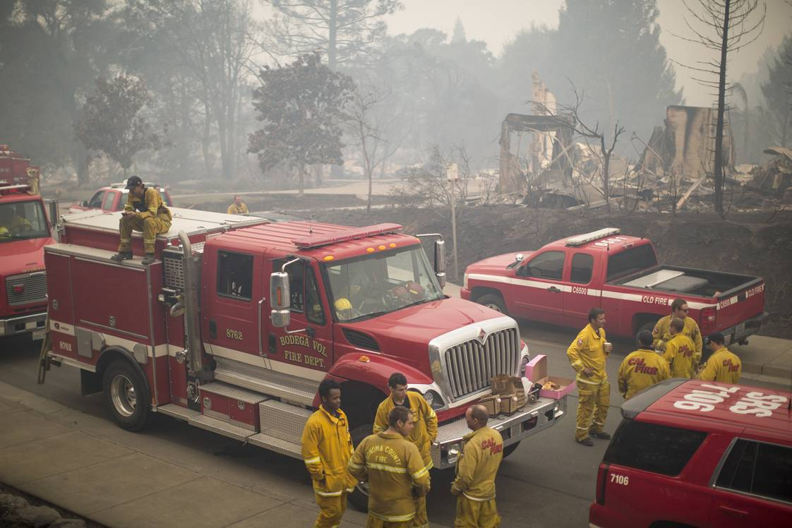 SANTA ROSA, CA -OCTOBER 10: Firefighters gather in a neighborhood of burned houses near Fire Station 5, which was also destroyed by fire, on October 10, 2017 in Santa Rosa, California. In one of the worst wildfires in state history, at least 1,500 homes have burned and 11 people have died as more than 14 wildfires continue to spread in eight Northern California counties.   (Photo by David McNew/Getty Images)