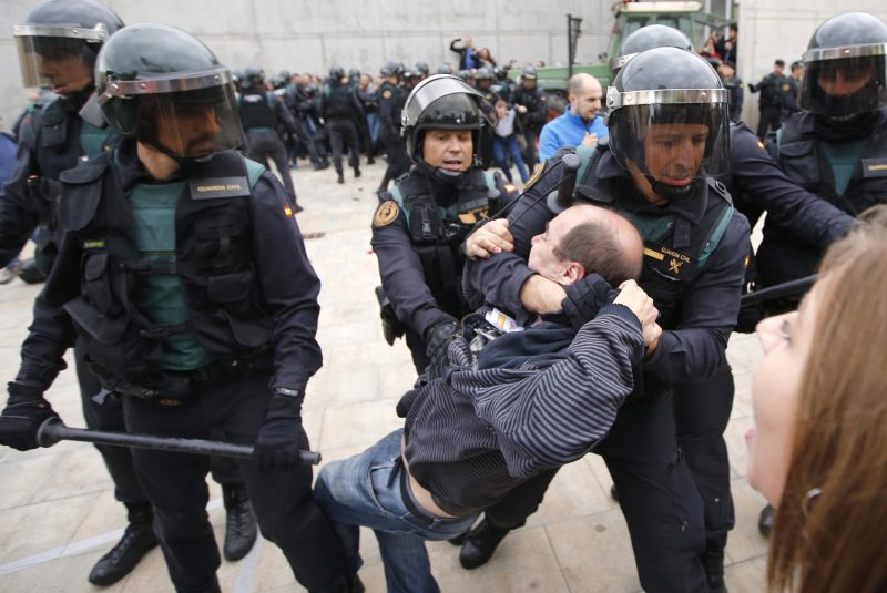 """Spanish Guardia Civil guards drag a man outside a polling station in Sant Julia de Ramis, where Catalan president was supposed to vote, on October 1, 2017, on the day of a referendum on independence for Catalonia banned by Madrid.  More than 5.3 million Catalans are called today to vote in a referendum on independence, surrounded by uncertainty over the intention of Spanish institutions to prevent this plebiscite banned by justice.  / AFP PHOTO / Raymond ROIG / """"The erroneous mention[s] appearing in the metadata of this photo by KENZO TRIBOUILLARD has been modified in AFP systems in the following manner: [RAYMOND ROIG] instead of [KENZO TRIBOUILLARD]. Please immediately remove the erroneous mention[s] from all your online services and delete it (them) from your servers. If you have been authorized by AFP to distribute it (them) to third parties, please ensure that the same actions are carried out by them. Failure to promptly comply with these instructions will entail liability on your part for any continued or post notification usage. Therefore we thank you very much for all your attention and prompt action. We are sorry for the inconvenience this notification may cause and remain at your disposal for any further information you may require."""""""