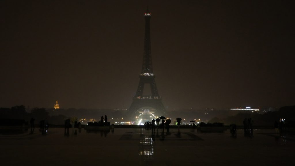 """The lights of the Eiffel Tower in Paris are switched off on October 2, 2017 in tribute to the victims of the attacks in Las Vegas and Marseille. At least 50 people were killed and hundreds wounded on October 1, when a gunman opened fire on a concert in Las Vegas in the deadliest mass shooting in modern US history. Earlier on October 1, a man knifed two young women to death outside the main train station in Marseille, France's second-biggest city. The Islamic State group claimed responsibility for both attacks via the jihadists' propaganda outlet Amaq, which said they were carried out by its """"soldiers"""". It did not provide any evidence for either claim. / AFP PHOTO / LUDOVIC MARIN"""