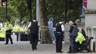 A police forensics officer (C) works at the scene of an incident at the junction of Exhibition Road and Cromwell Road, between the Victoria and Albert (V&A) Museum and the Natural History Museum, in the South Kensington district of London on October 7, 2017.Police arrested a man near London's Natural History Museum on Saturday after a vehicle apparently drove into pedestrians, injuring a number of people. Crowds in the busy tourist spot in South Kensington, which is also home to the Victoria & Albert Museum and the Science Museum, fled screaming in panic, an AFP reporter said. / AFP PHOTO / Tolga AKMEN