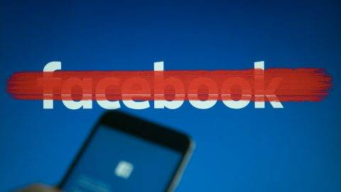 An iphone with a facebook login screen is seen with a striked out facebook logo in the background in this photo illustration on September 22, 2017. (Photo by Jaap Arriens/NurPhoto)