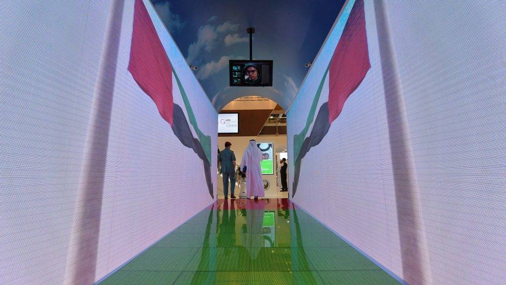 A policeman and visitor walk through a security tunnel at the Gitex 2017 exhibition at the Dubai World Trade Center in Dubai on October 10, 2017. Travellers departing from Dubai will no longer need to pass through any sort of security clearance, they will walk through a virtual aquarium tunnel that will scan their face or iris using 80 hidden cameras while they're in motion.  / AFP PHOTO / GIUSEPPE CACACE