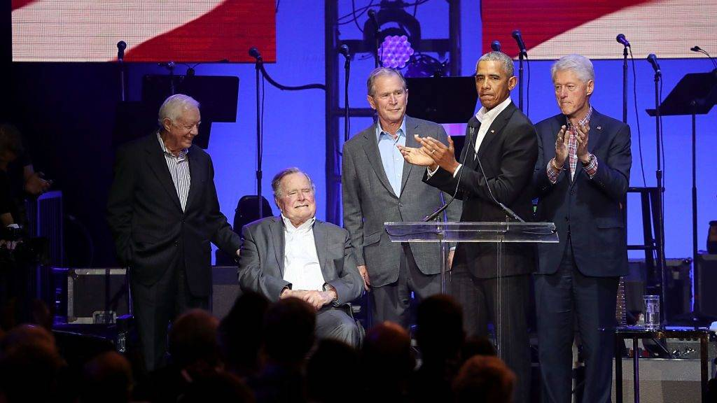 """COLLEGE STATION, TEXAS - OCTOBER 21:  (L - R) Former United States Presidents Jimmy Carter, George H.W. Bush, George W. Bush, Barack Obama and Bill Clinton address the audience during the """"Deep From The Heart: One America Appeal Concert"""" at Reed Arena on October 21, 2017 in College Station, Texas.  (Photo by Gary Miller/Getty Images)"""