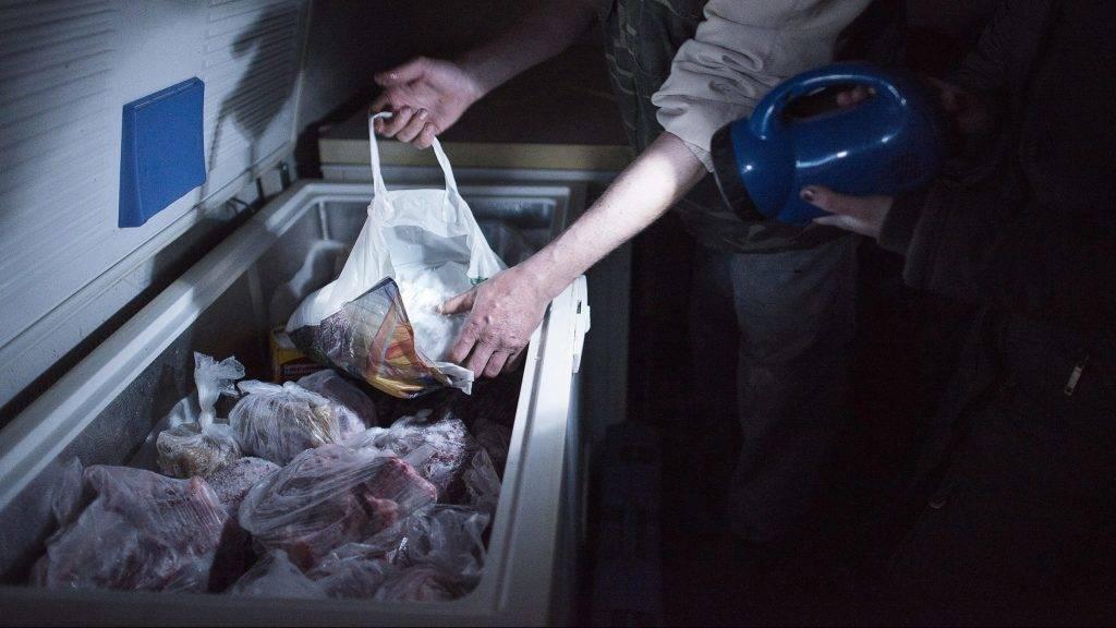Paszab, 2013. március 17. Ifj. Németh Zoltán (b) és Szuhi Éva mûanyag zacskóba töltött hóval hûti a fagyasztóban lévõ húst paszabi házuk fészerében 2013. március 17-én. Az önkormányzat hat aggregátort kapott a katasztrófavédelemtõl, ezeket viszik körbe a településen mindig oda, ahol a legnagyobb szükség van rá. Az áramszünet szempontjából legkritikusabb, az ibrányi járáshoz tartozó 1300 lakosú Paszabon négy napja nincs áram egyetlen háztartásban sem. MTI Fotó: Balázs Attila