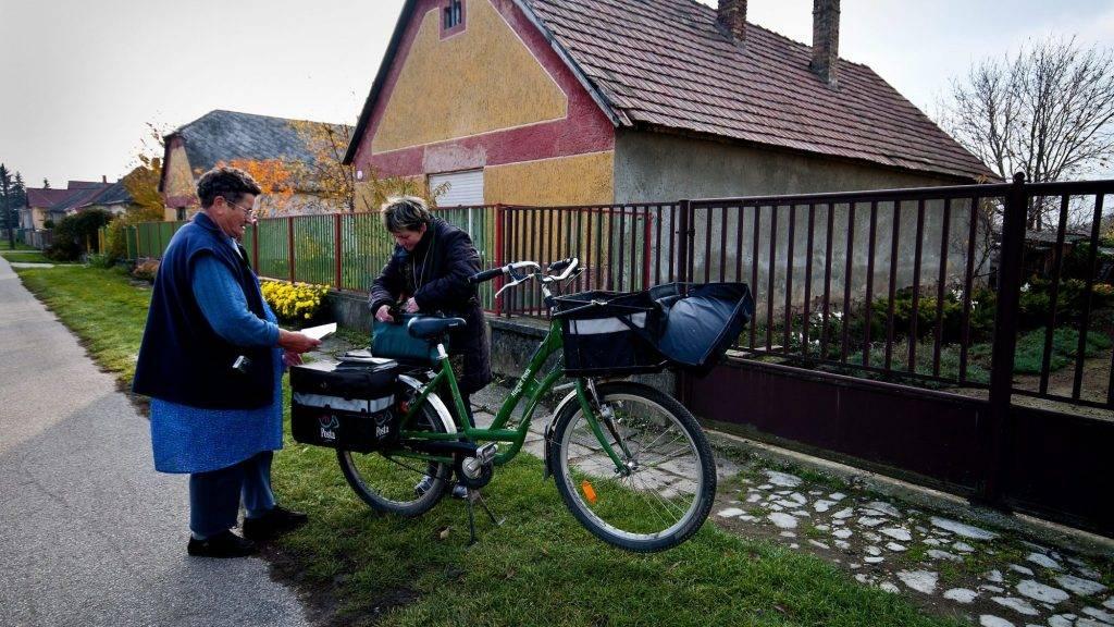 Tárkány, 2012. november 16. Postás kézbesíti egy idõs nõ nyugdíját Tárkányban 2012. november 16-án. A Komárom-Esztergom megyei községben idõközi választást tartanak november 25-én, a polgármesteri székért 3 jelölt indul. MTI Fotó: Krizsán Csaba