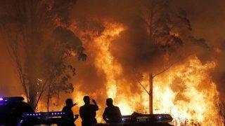 Chandebrito, 2017. október 16. Spanyol polgárõrök nézik az égõ növényzetet az Északnyugat-Spanyolországban pusztító erdõtüzek egyik fészkénél, a galíciai Chandebrito település közelében 2017. október 15-én. A szárazság és enyhe hõmérséklet miatt gyorsan terjedõ lángok eddig mintegy négyezer hektárnyi területet perzseltek fel a térségben. (MTI/EPA/Lavandeira Jr.)