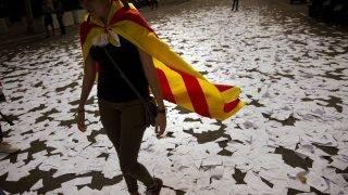 Barcelona, 2017. október 3. A függetlenségpárti tüntetõk által a spanyol kormányzó Néppárt barcelonai épülete elõtt szétszórt szavazólapokon megy egy katalán zászlót viselõ nõ 2017. október 3-án. A Katalónia függetlenségérõl tartott népszavazás alatt elkövetett spanyol rendõri brutalitás miatt általános sztrájk van a régióban. (MTI/AP/Emilio Morenatti)