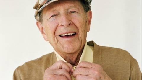Senior man wearing hat, doing up shirt button, smiling, portrait