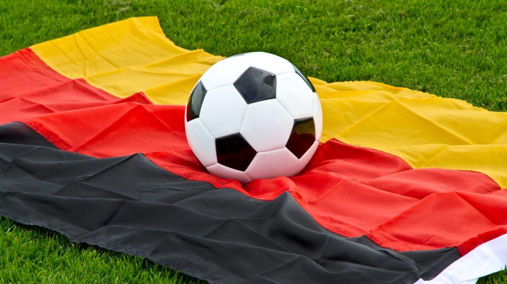 Soccer ball lying on a german flag in stadium