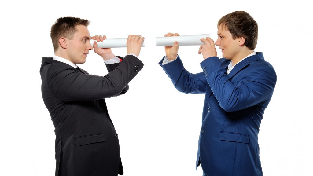 Two businessmen looking through a rolled paper. Business vision, competitors tracking or headhunters concept.