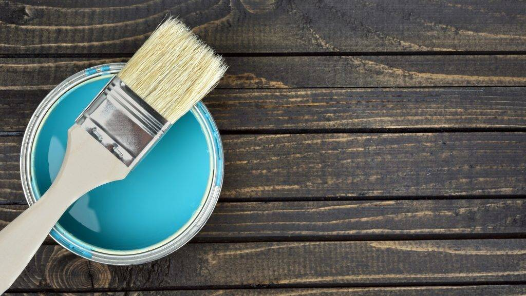 Paint bucket and brush on wooden table