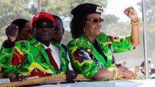 Zimbabwe President Robert Mugabe (L) with his wife Grace Mugabe (R) raise their fists in a vehicle before meeting delegates during a Zimbabwe ruling party Zimbabwe African National Union Đ Patriotic Front (ZANU-PF) youth rally at Rudhaka Stadium in Marondera on June 2, 2017. Zimbabwean President Robert Mugabe on June 2, 2017 launched a nationwide 10-venue speaking tour aimed at drumming up support ahead of elections next year when he plans to seek office again. The 93-year-old leader, who appeared in better health than at some recent public appearances, spoke for an hour and a half at a rally outside Harare attended by several thousand ZANU-PF supporters.  / AFP PHOTO / Jekesai NJIKIZANA