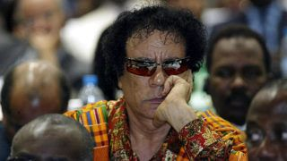 Libyan Leader Moammer Kadhafi listens to speeches at the Maputo conference Center 12 July 2003 on the second and last day of the 2nd Heads of states and governments of the African Union summit. The second African Union (AU) summit being held in the Mozambique capital ended 12 July with heads of state appointing a leadership assigned to set up AU organs such as a Peace and security Council. / AFP PHOTO / ALEXANDER JOE