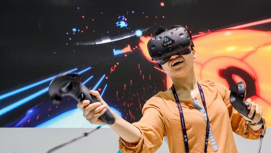 --FILE--A visitor tries out an HTC VR (Virtual Reality) device during the 2016 Mobile World Congress (MWC) in Shanghai, China, 29 June 2016.  HTC has signed a partnership with Chinese e-commerce giant Alibaba that will see HTC use Alibaba's cloud computing services for its nascent virtual reality unit. The struggling Taiwanese smartphone maker has been trying to make headway into the virtual reality space with its HTC Vive headset as its core smartphone business continues to weaken. To help spur more mainstream interest in VR (and thus, to help boost sales), HTC has rolled out several big initiatives. In April, HTC created a $100 million investment fund for VR-focused startups, and in July, HTC said it would open over 10,000 HTC Vive demo stores in China so residents could try out the devices. By partnering with Alibaba's cloud computing arm, HTC said that the two companies will work together to improve the behind-the-scenes data center infrastructure required to deliver virtual reality content to consumers.