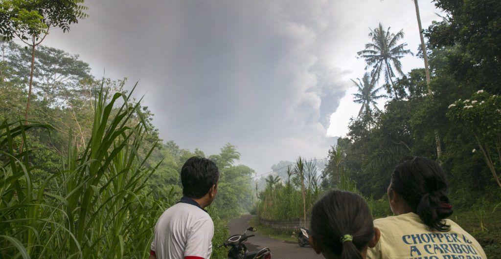 Karangasem, 2017. november 26. Falubeliek nézik, amint az Agung-hegy tûzhányója hamut és füstöt lövell a légtérbe a Bali szigetén fekvõ Karangasemnél 2017. november 26-án. Egy napon belül négyszer is kitört a vulkán, ezért több légitársaság törölte az indonéz szigetet érintõ járatait. (MTI/EPA/Made Nagi)