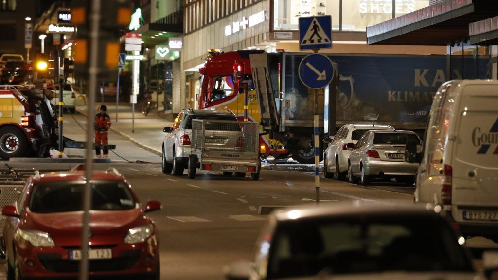 A tow truck (L) arrives on April 8, 2017, to remove the stolen truck (R) which was driven through a crowd outside a department in Stockholm on April 7, 2017. A massive manhunt was underway for the driver of the stolen truck that ploughed into the crowd, killing four and injuring 15, Swedish police said. / AFP PHOTO / Odd ANDERSEN