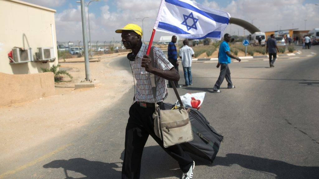 An African illegal migrant walks with the Israeli flag following his release from the Holot Detention Centre in Israel's Negev desert, on August 25, 2015. Israel began releasing hundreds of African migrants from the detention centre after a court order, but the asylum-seekers were barred from entering two cities. A recent court decision ordered Israel to release the illegal migrants held for more than a year at a detention centre in the Negev desert, a ruling affecting 1,178 of the asylum-seekers.  AFP PHOTO/MENAHEM KAHANA / AFP PHOTO / MENAHEM KAHANA