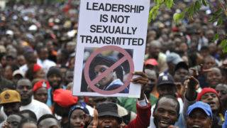 People hold an anti-Grace Mugabe placard during a demonstration demanding the resignation of Zimbabwe's president  on November 18, 2017 in Harare. Zimbabwe was set for more political turmoil November 18 with protests planned as veterans of the independence war, activists and ruling party leaders called publicly for Zimbabwe's President to be forced from office. / AFP PHOTO / ZINYANGE AUNTONY