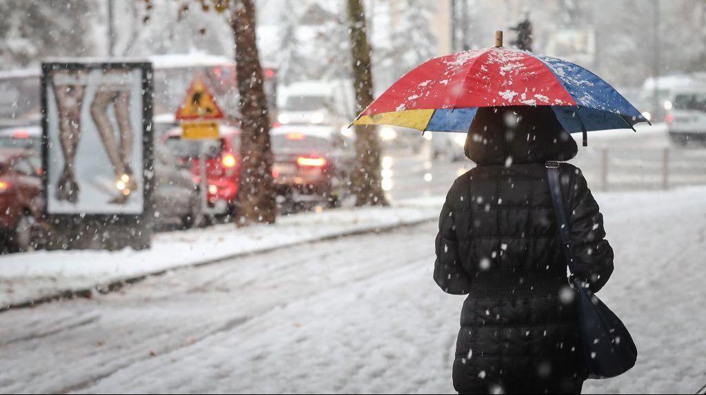 LJUBLJANA, SLOVENIA - NOVEMBER 13: A woman with an umbrella walks in a street after the first snowfall of the season on an autumn day in Ljubljana, Slovenia on November 13, 2017. Ales Beno / Anadolu Agency