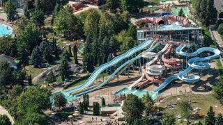 Hajdúszoboszló, 2017. augusztus 17. Elõtérben az Aquapark csúszdái, balra fürdõzõk a Hajdúszoboszlói Gyógyfürdõ strandján. A pihenni, szórakozni vágyókat 13 medence 13.000 négyzetméternyi vízfelülete várja az Aquapark szolgáltatásai mellett.                                  MTVA/Bizományosi: Oláh Tibor  *************************** Kedves Felhasználó! Ez a fotó nem a Duna Médiaszolgáltató Zrt./MTI által készített és kiadott fényképfelvétel, így harmadik személy által támasztott bárminemû – különösen szerzõi jogi, szomszédos jogi és személyiségi jogi – igényért a fotó készítõje közvetlenül maga áll helyt, az MTVA felelõssége e körben kizárt.