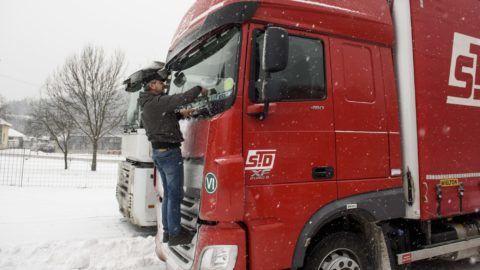 Somoskõújfalu, 2017. január 13. Jármûve szélvédõjét tisztítja egy várakozó kamionsofõr Somoskõújfaluban 2017. január 13-án. Az idõjárási körülmények miatt Pest, Heves és Nógrád megyében 7,5 tonnás súlykorlátozást vezettek be több úton is - közölte az Útinform. A szlovák hatóságok döntése értelmében Parassapusztától Bánrévéig valamennyi határátkelõhelyen hasonló korlátozást vezettek be: a 7,5 tonnánál nehezebb jármûvek nem hajthatnak be Szlovákiába. MTI Fotó: Komka Péter
