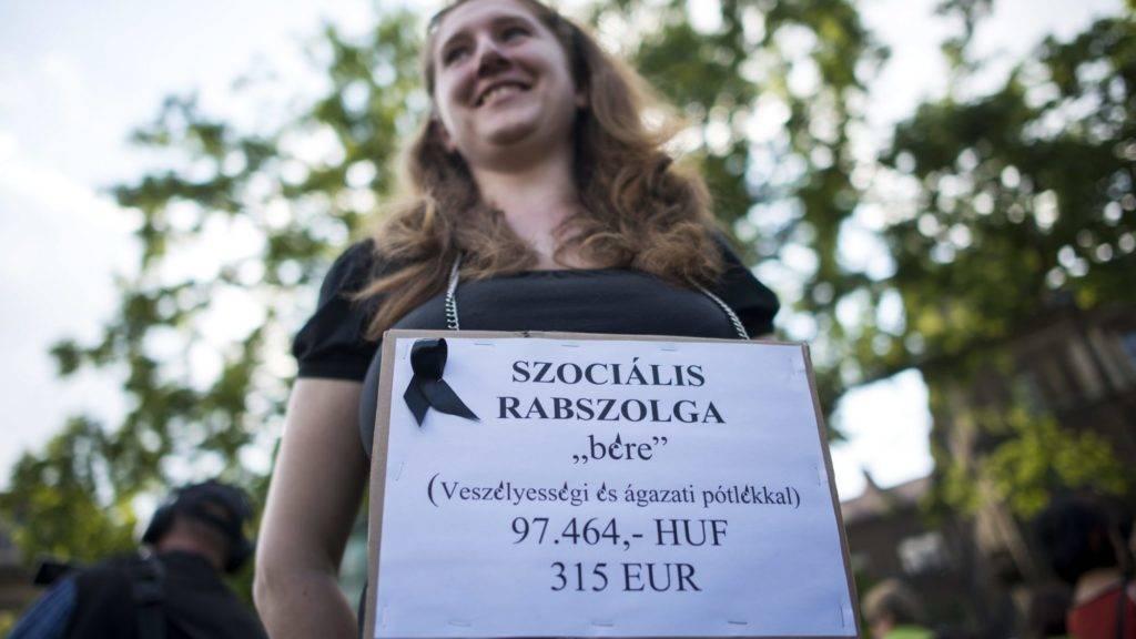 """Budapest, 2015. május 29. """"Szociális rabszolga"""" felirat egy résztvevõ nyakában a szociális ágazatban dolgozók demonstrációján a fõvárosi Kodály köröndön 2015. május 29-én. MTI Fotó: Marjai János"""