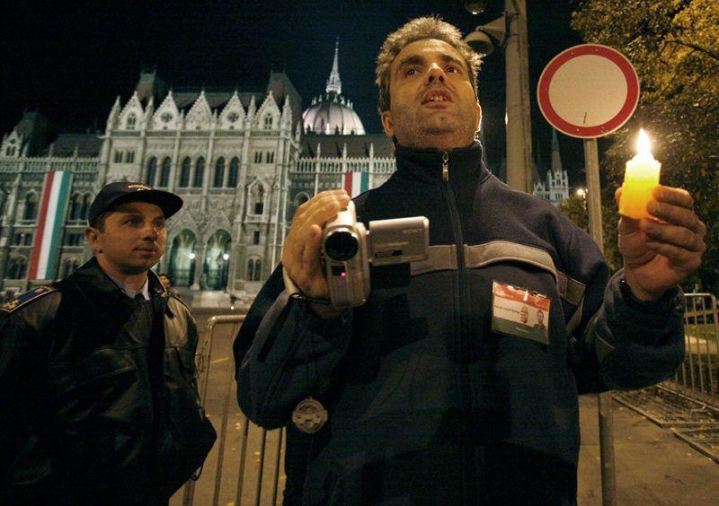 Budapest, 2006. október 26.Kalmár László György, a tüntetők egyik képviselője rendőri engedéllyel, felügyelet mellett indul megemlékezni az elzárt, műveleti területen az ötven évvel ezelőtti sortűz áldozatairól az 1956-os emlékműnél október 25-én éjjel a Kossuth Lajos téren a Parlamentnél.MTI Fotó: Füzesi Ferenc
