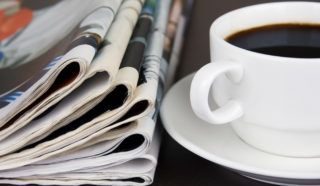 Pile of newspapers and cup of coffee on the table.