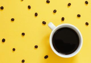 Top view of black coffee and coffee beans on yellow background