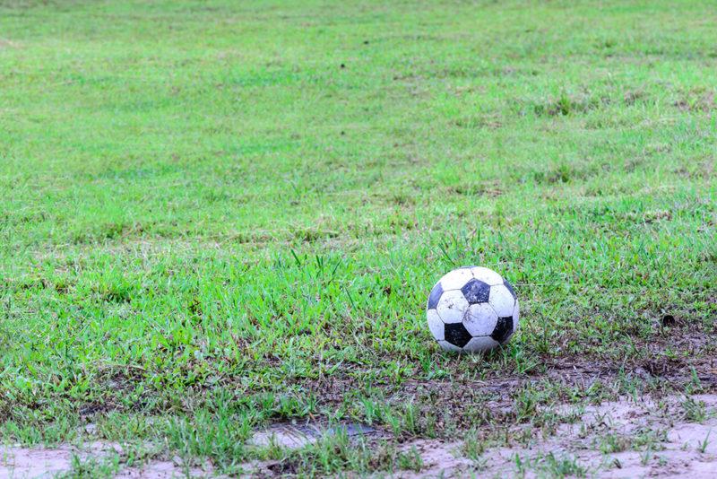 Dirty soccer ball in wet field.