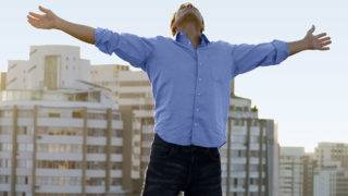 Man on roof with arms outstretched